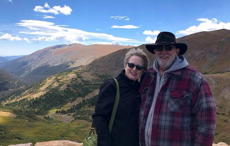 Jim, who had nonalcoholic fatty liver disease, with his wife with the mountains behind them.