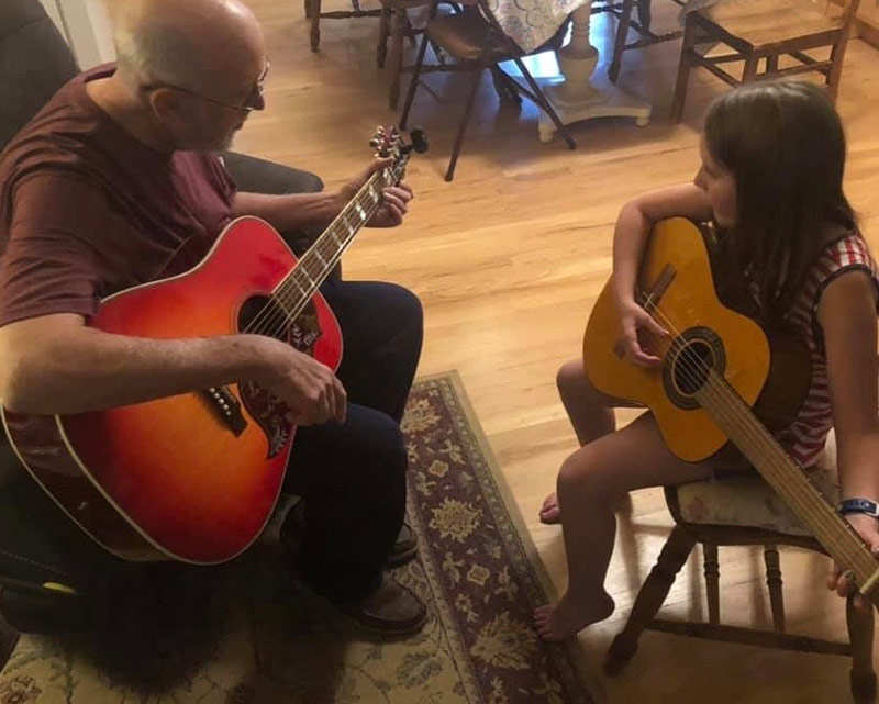 Jim playing guitar with his granddaughter in the kitchen.