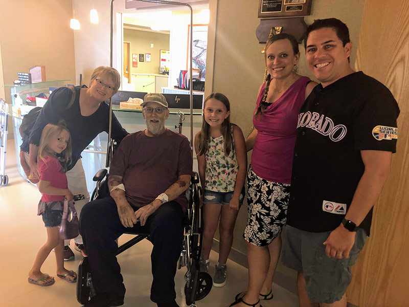 Jim in a wheelchair after treatment for nonalcoholic fatty liver disease with his family by his side.