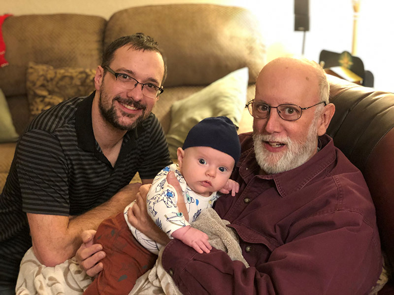 Jim holding his newest grandchild and his son.