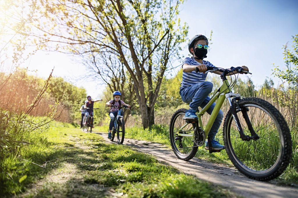 Kids ride bikes outdoors while wearing masks and practicing social distancing, demonstrating two ways to keep kids safe during this COVID-19 summer..