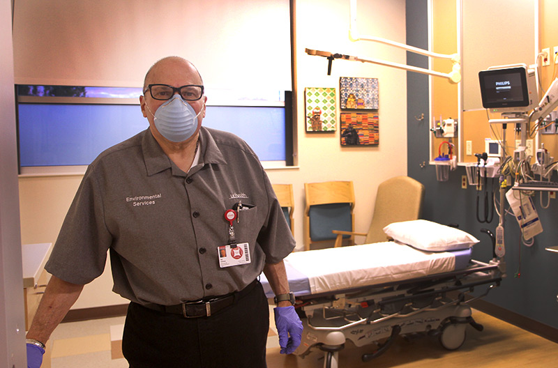 Sal standing in ER room as a EVS technician.