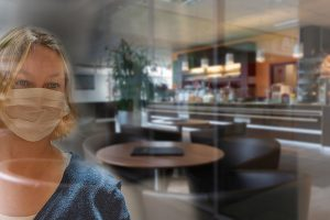 Concerns about airborne COVID-19 are increasing. Here, a woman wearing a masks gazes inside an empty restaurant.