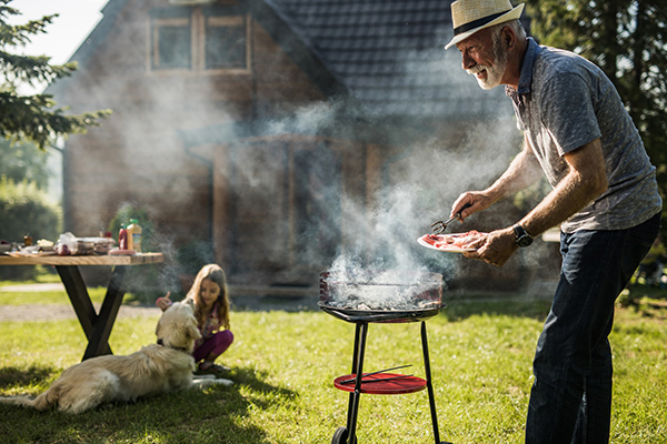 Grilling myths busted. An older man grills with a little girl and a dog in the backround.