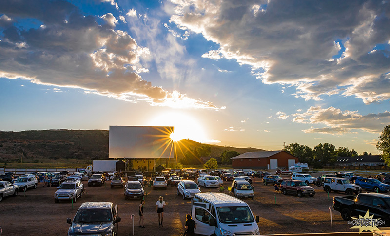 Drive-in theater in Fort Collins set up for live music concert, with sun setting behind the stage.