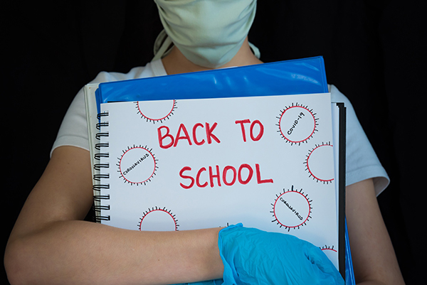 "Is school safe during the COVID-19 pandemic? A girl with wearing a mask holds a binder that says ""Back to School."""