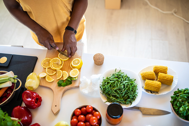 cutting lemons, with other vegetables on the table, as part of flavor pairing.