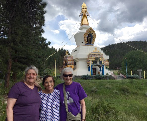 three women stand in front of the Shambhala Center.