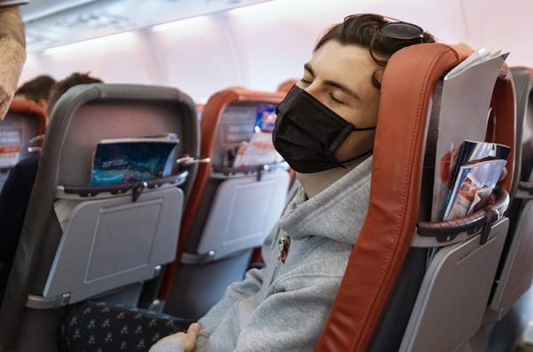 man sleeping with mask on a plane - airborne covid