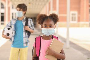 young girl and boy outside a school wearing masks; is school safe