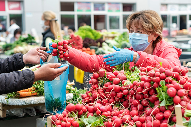 Colorado farmers markets - A woman wearing a medical mask buyes bright red radishes