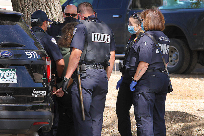police and community paramedics talk to a person in a behavioral health crisis on the streets in Fort Collins.