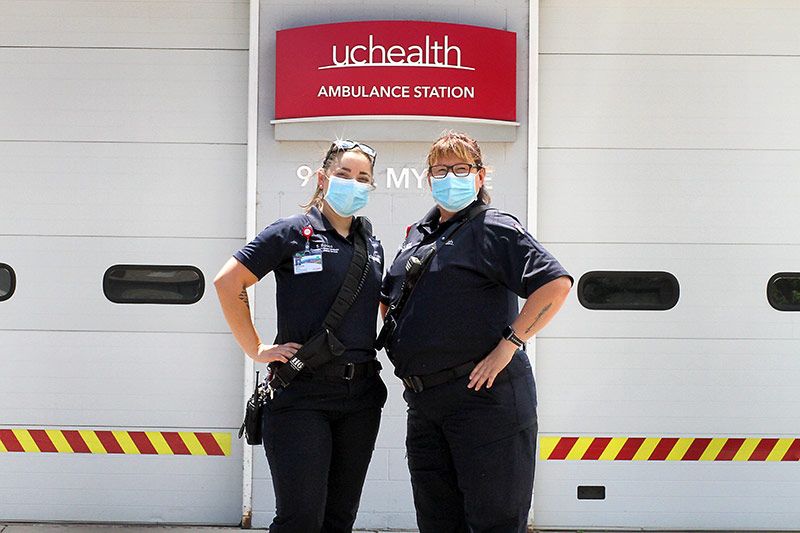 two community paramedics stand outside their UCHealth station.