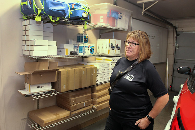 community paramedic stands in the garage with in-home monitoring supplies they use on the shelf.