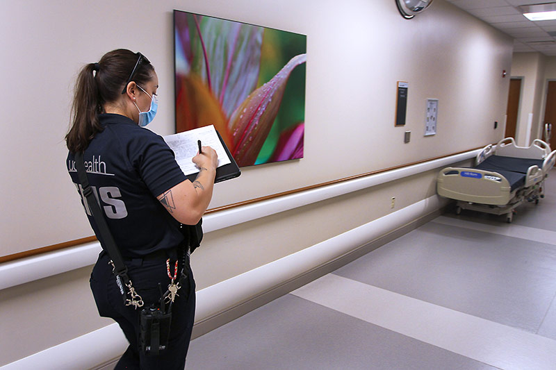 UCHealth community paramedic fills out a mental health hold paperwork in the hallway of Poudre Valley Hospital.