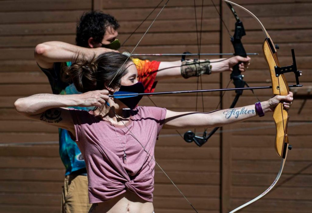 Hannah Moraski and her soon-to-be husband, Justin Smith, practice archery. Because of a new prescription drug, Givlaari, Hannah has a vast appreciation for her newfound freedom (even in a pandemic).