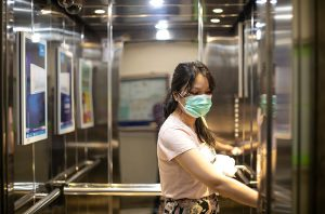 woman wearing mask in an elevator, a place were airborne coronavirus transmission would be more likely to happen.