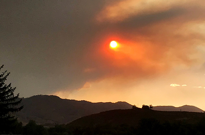 smoke from a wildfire cover the sky and turns the sun orange, adding safety risks during coronavirus pandemic