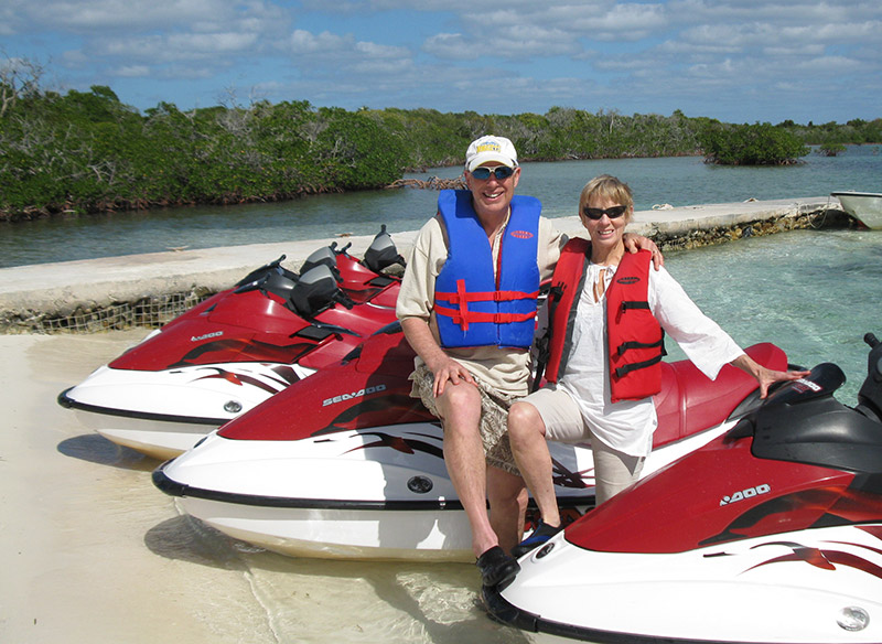 Dave with wife sitting on jetskis on sandy beach.