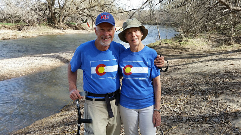 Dave with his arm around his wife at the poudre river, both wearing colorado shirts. It wasn't until about four years ago that Voni was diagnosed with vascular dementia and Dave started to seek tools for caregivers.