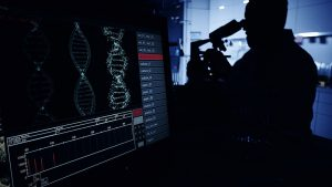 man looking into a microscope at coronavirus mutation, while DNA shows on the screen.