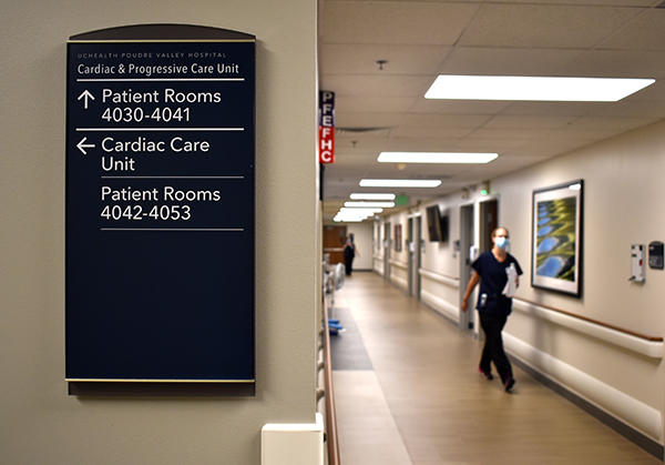 Nurse walks down hallway. A navigational sign on the wall points to new cardiac unit and new progressive care unit in the newly renovated wing of PVH..