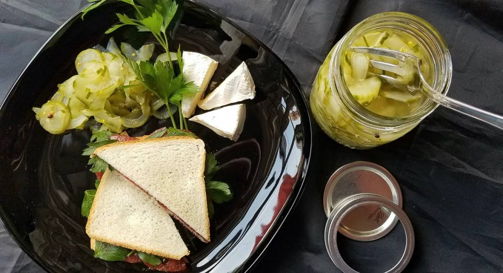 Quick homemade pickles. A photo of quick homemade pickled vegetables next to a sandwich and brie.