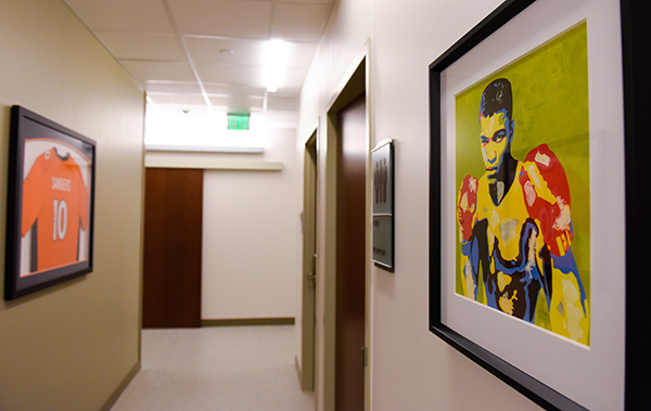 new medical center Cherry Creek - A painting of Muhammad Ali and a Broncos jersey decorate walls.
