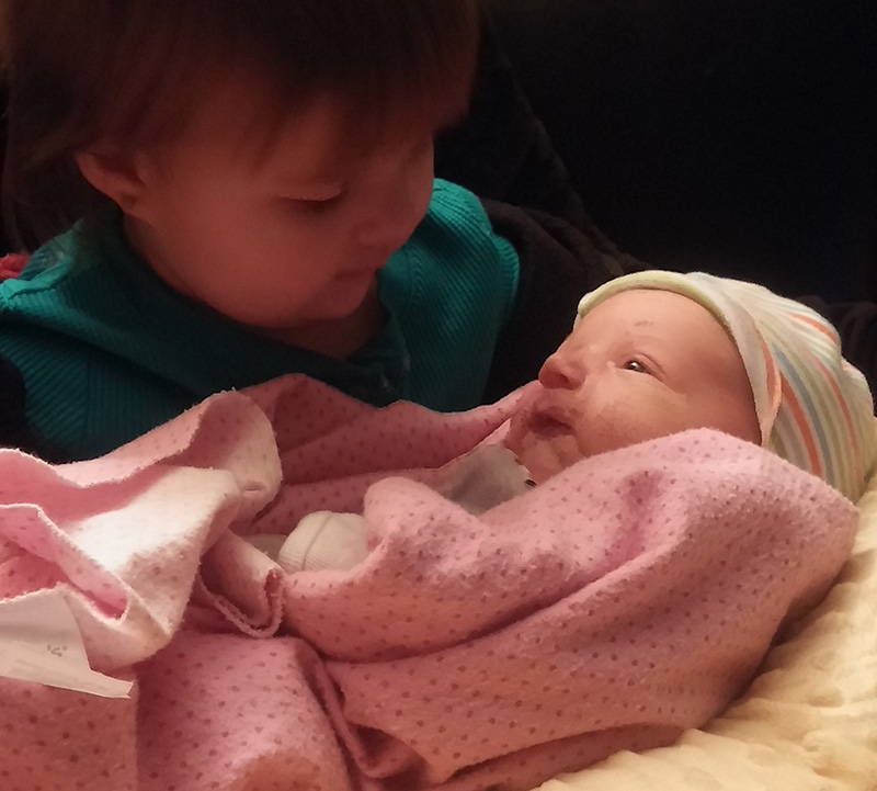 Abby Zamora has loved having a nurse midwife-assisted births. Here her third child admires a new baby.