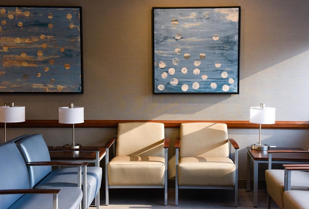 A waiting room with chairs and art in the UCHealth Cherry Creek Medical Center.