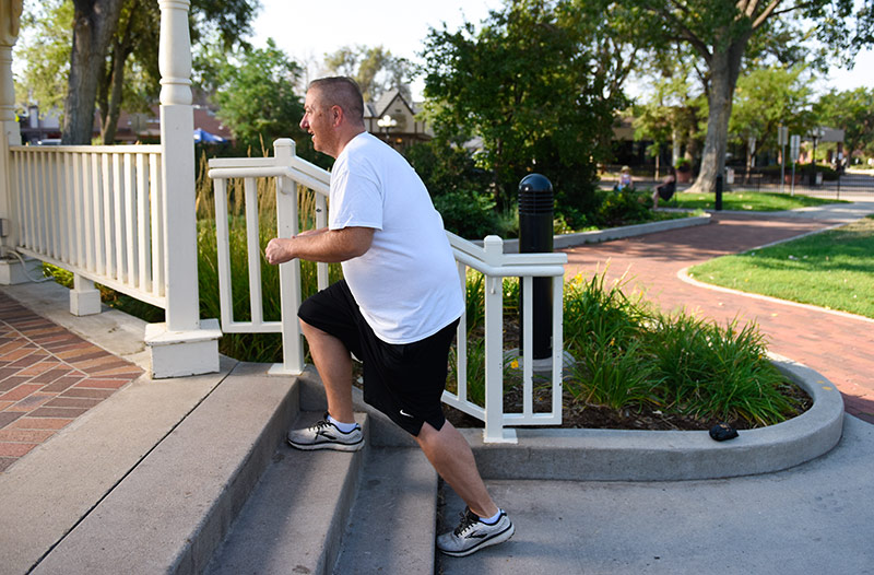 man works out on stairs at a park after his cartilage transplant.
