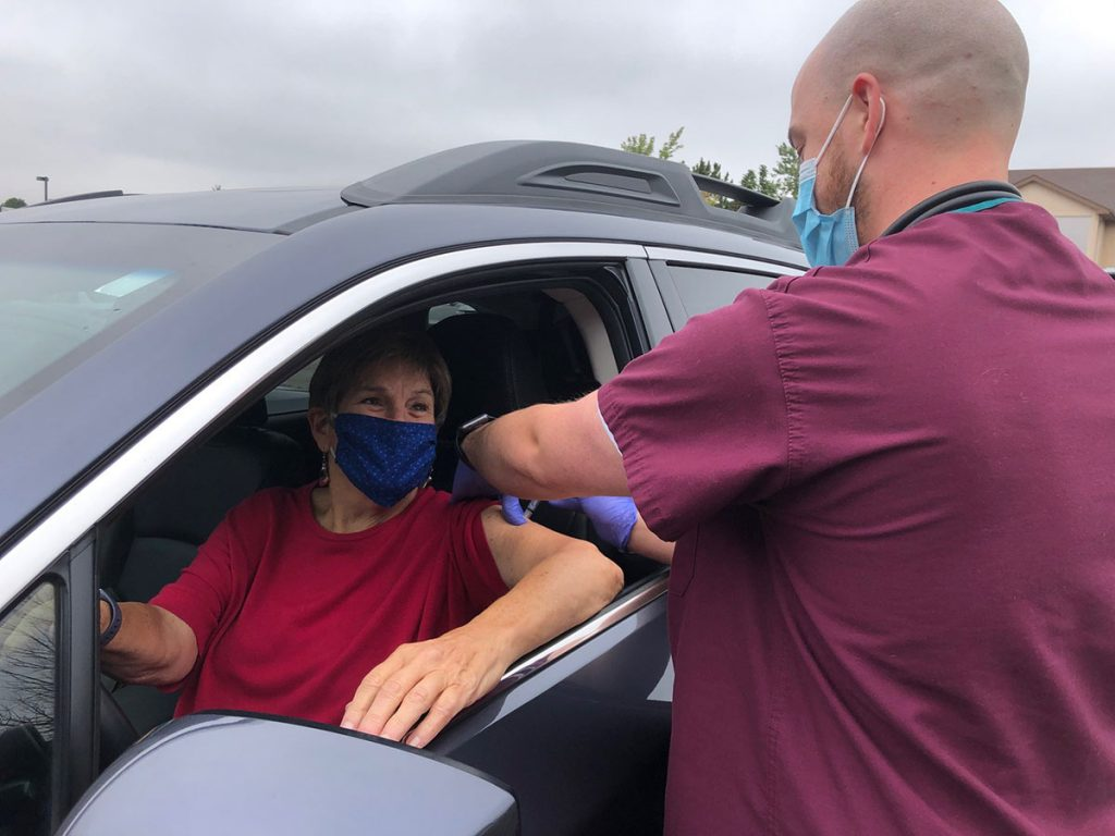 Woman gets her flu shot while sitting in her car, by way of a nurse. She is one of many getting flu shots curbside this year.