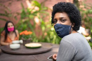 to prevent superspreader events, wear masks, avoid creeds, stay apart and gather outside. Some women wearing masks sit at an outdoor table.