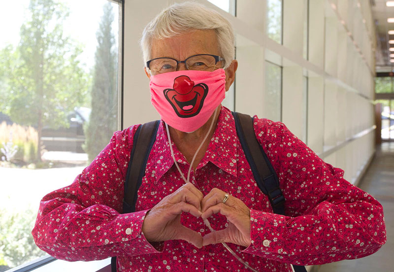 Fran, who has battled cancer, heart disease and pulmonary arterial hypertension, wears a clown mask and holds her hands in a heart shape while at the hospital.