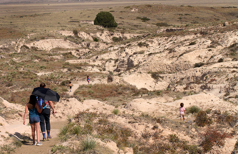people walk down a trail into an arroyo at The Pawnee Buttes.