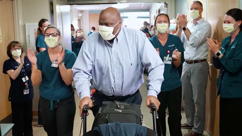 UCHealth staff celebrated as a man leaves the hospital with a walker. He is one of 2,001 UCHealth COVID survivors as of Oct. 6, 2020.