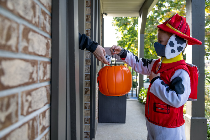 Child in paw patrol outfit gets a bag of candy from a hand out the door. UCHealth provides tips on how to do Halloween safely during covid.