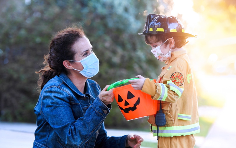 boy in a firefighter costume wearing a mask with his mother, also wearing a mask. Both demonstrating how to do halloween safely during COVID.