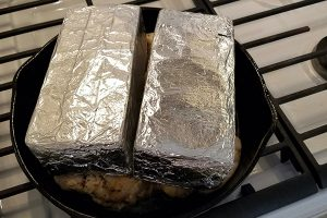 Try roasting chicken under a brick in your oven like shown here with a cast iron skillet, chicken laid flat and brings wrapped in foil on top of the chicken.