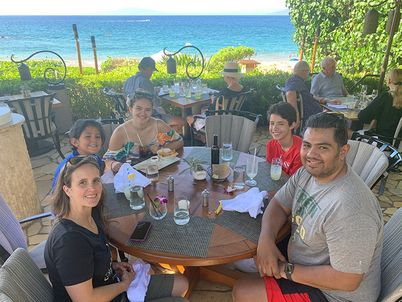family sits around a table in Hawaii