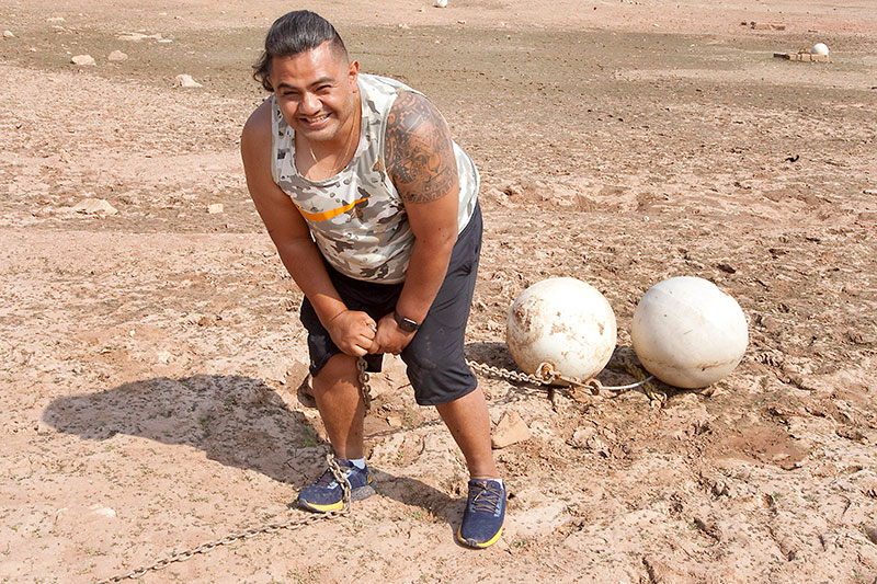 Edgar pulling two large balls on chains on a beach with a grin on his face.
