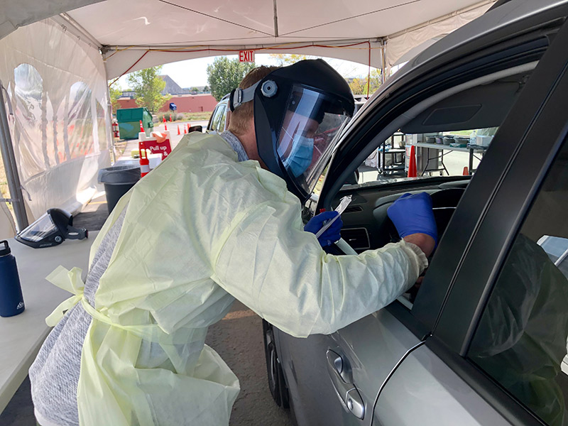Testing is essential in the fight against COVID-19. Here a health worker in protective gear tests a person in a car at a UCHealth hospital.