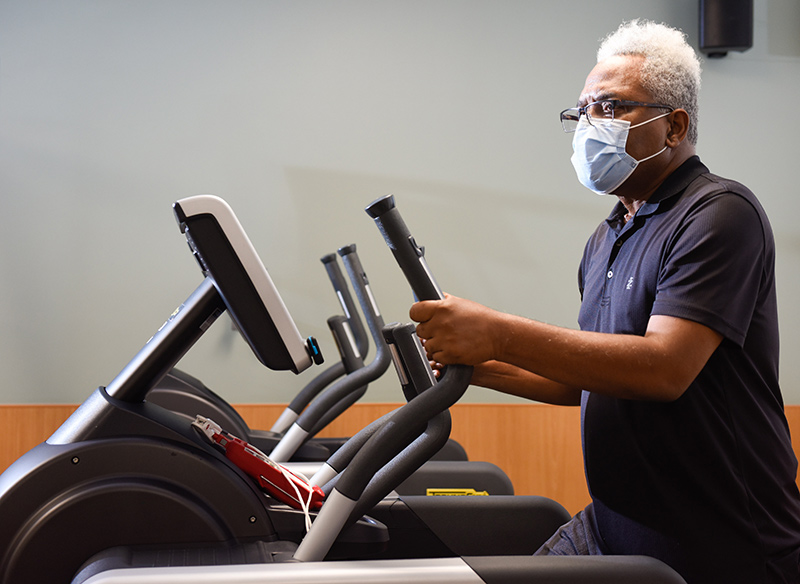 Clarence Troutman working out on a stair stepper. He's dealing with long-term symptoms of COVID-19, a group of patients who identify themselves as COVID-19 'long-haulers.'