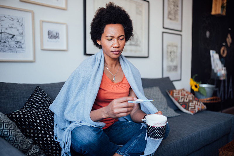 Woman sick on her couch at home. Medical experts give advice on how to tell the difference between flu, a cold or COVID-19.
