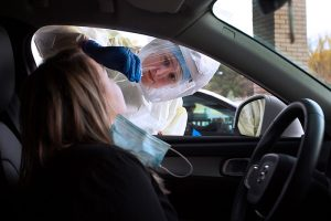 UCHealth employee tests a patient for COVID-19 at a drive-thru testing site.
