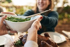 Holiday gatherings in 2020 will need to be smaller and safer, like this celebration outside. A person hands green beans over a turkey at a table outdoors.
