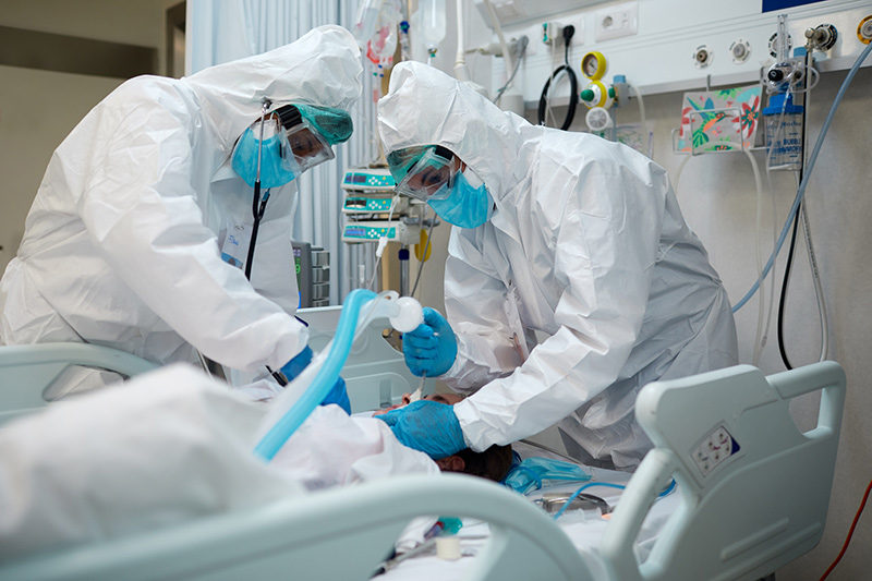 Doctors working on a COVID-19 patient. The Colorado coronavirus model shows we must act now or many people will end up in ICUs. Here, a patient with COVID-19 gets intubated in an ICU.