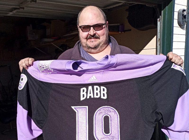 Derek holding a Hockey Fights Cancer jersey.