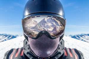 This close-up photo shows a skiier wearing a helmet, goggles and facemask over the nose and mouth, safe skiing practices during the coronavirus pandemic..
