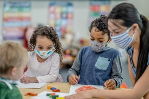 Asymptomatic COVID-19 infections are common in people of all ages, including children. Here, children wear masks while they color at school.
